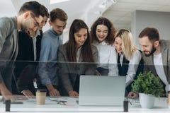 Het samenwerken Groep jonge moderne mensen in slimme vrijetijdskleding die zaken bespreken en in het creatieve bureau glimlachen stock afbeelding