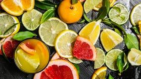 Het sap van citrusvruchten - grapefruit, sinaasappel, mandarijn, citroen, kalk in het glas Stock Foto's