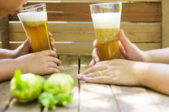 Het sap van de holdingsnoni van de vrouwen` s hand en kind het drinken nonisap met nonifruit op houten lijst Stock Foto's