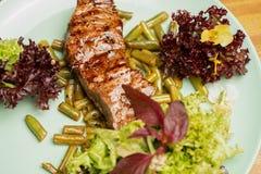 Het sappige geroosterde lapje vlees van het rundvleesachterdeel met verse die salade en snijbonen met viooltjebloem wordt versier stock afbeelding