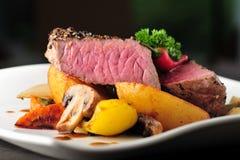 Sappig lapje vlees met aardappelen in de schil en paddestoelen Stock Foto
