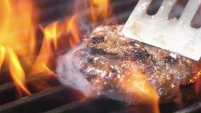 Het sappige smakelijke vlees voor een Hamburger wordt omgekeerd op de grill met een spatel