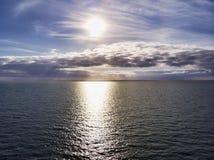 Het satellietbeeld boven oceaan, met bewolkte pastelkleur gekleurde toneelhemel en zonstralen raakt het water in een hete de zome royalty-vrije stock foto's