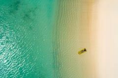 Het satellietbeeld van het slanke vrouw zwemmen op zwemt matras in het transparante turkooise overzees in Seychellen De zomerzeeg stock foto