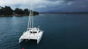 Het satellietbeeld van verankerde een catamaranjacht status en de mensen kunnen zonnebadend op het zijn dek stock video