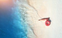 Het satellietbeeld van vrouw met zwemt ring op het zandige strand royalty-vrije stock foto