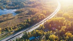 Het satellietbeeld van weg in mooi de herfst bos Mooi landschap met asfalt landelijke weg, bomen met rood en sinaasappel gaat weg royalty-vrije stock afbeeldingen