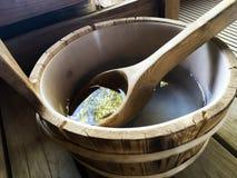 Het saunabinnenland ontspant in Finse sauna houten emmer met aard die in water voor gezondheid en het helen nadenken Stock Afbeelding