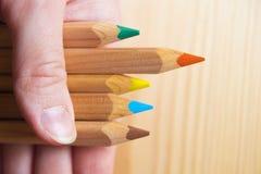 Het schaak stelt bischoppen voor Hand die houten kleurrijke potloden houden tegen houten achtergrond Rood potlood die boven ander Stock Afbeelding