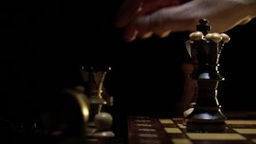 Het schaakbord en het schaak, een mensen` s hand maken een beweging van een houten cijfer stock video