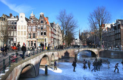 Het schaatsen dichtbij de kruising van twee kanalen in Amsterdam Stock Fotografie