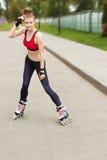 Het schaatsende meisje van de rol in park het rollerblading op gealigneerde vleten Gemengde ras Aziatische Chinese/Kaukasische vr Stock Afbeeldingen