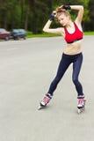 Het schaatsende meisje van de rol in park het rollerblading op gealigneerde vleten Gemengde ras Aziatische Chinese/Kaukasische vr Royalty-vrije Stock Foto