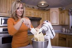 Het schavende deeg van de vrouw in mixer stock fotografie