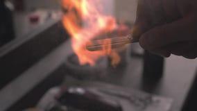 Het scheermesdesinfectie van het close-uphulpmiddel met behulp van een roosterende brand in de de herenkapper of salon van mensen stock videobeelden