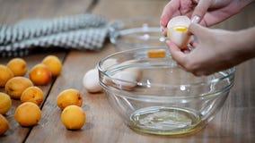 Het scheiden van dooier en wit van het witte shell ei met vrouwenhanden boven metaalroestvrij staal die kom mengen stock videobeelden
