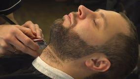 Het scheren van baard van de mens in kapperswinkel stock footage