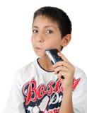 Het scheren van de jongen wang met zijn scheermes en pret Stock Foto