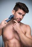 Het scheren van de mens met scheerapparaat stock afbeelding