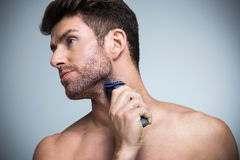 Het scheren van de mens met scheerapparaat stock foto