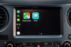 Het scherm van Apple Carplay in autodashboard die Google Maps en Waze tonen apps stock foto