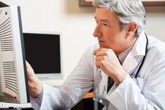 Het Scherm van artsenlooking at computer Stock Foto