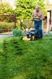 Het scherpe gras van de mens met de maaimachine Royalty-vrije Stock Afbeeldingen