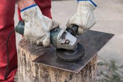 Het scherpe metaal van de arbeider met molen royalty-vrije stock foto's