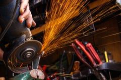 Het scherpe metaal van de arbeider met molen Vonkt terwijl het malen van ijzer S Stock Foto's