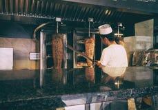 Het scherpe vlees van de kebabchef-kok stock afbeelding