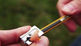 Het scherpen van een potlood met een slijper in het park stock video