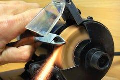 Het scherpen van zij scherpe buigtang op elektro malend wiel stock afbeelding