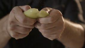 Het scheuren van gele groene paprika in de helft stock video