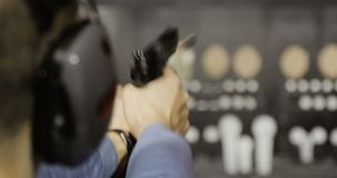 Het schieten met een pistool Een close-up van een pistool in zijn hand men kan de brand aan het vat merken stock footage