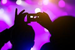 Het schieten op het overleg van het smartphonefestival De vage achtergrond van het muziekstadium bokeh voor ontwerp stock afbeelding