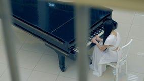 Het schieten van bovengenoemd van het meisje die de piano spelen Geen gezicht 4K stock videobeelden