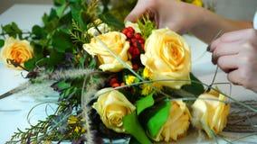 Het schieten van close-up van proces van decoratie van bloemmeisje door bloemist van bloemboeket van rozen in bloemwinkel i stock footage