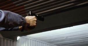 Het schieten van doelstellingen in een waaier Een close-up van een pistool in zijn hand men kan de brand aan het vat merken stock video