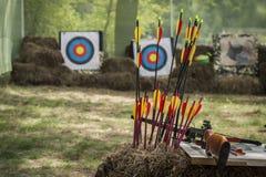 Het schieten van een kruisboog en heldere gekleurde pijlen in een plattelander die waaier in openlucht schieten Stock Foto