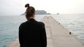 Het schieten van het achtervrouw lopen op overzeese kust die afstand onderzoeken stock videobeelden
