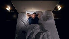 Het schieten van hierboven van de man die naar slaap proberen te gaan 4K stock videobeelden