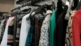 Het schieten van kleren in opslag, lange lijn met zwarte hangers met kleding stock footage