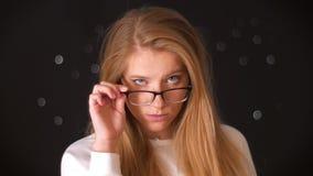 Het schieten verdenkend blik van blonde Kaukasische vrouw die en haar glazen met één hand bevinden zich houden terwijl het kijken stock video