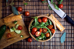 Het schikken van verse groene salade met komkommers en tomaten Stock Foto