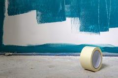 Het schilderen de werken aangaande een muur Met een broodje van buisband in de voorgrond Lopende het werk stock foto's