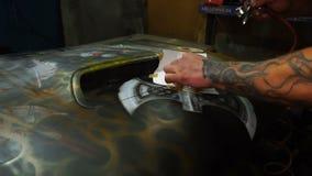 Het schilderen gebruikend luchtpenseel op de kap met een malplaatje stock video
