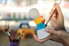 Het schilderen kleur op pleisterpop stock fotografie
