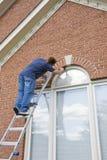 Het schilderen van de schilder versiering rond deurenvensters Stock Foto's