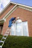 Het schilderen van de schilder versiering rond deurenvensters Stock Afbeeldingen