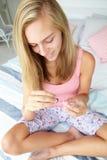 Het schilderen van de tiener spijkers op bed Stock Foto